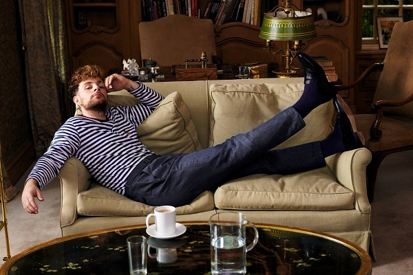 Tom Grennan laying on a sofa wearing a striped top, and blue trousers.