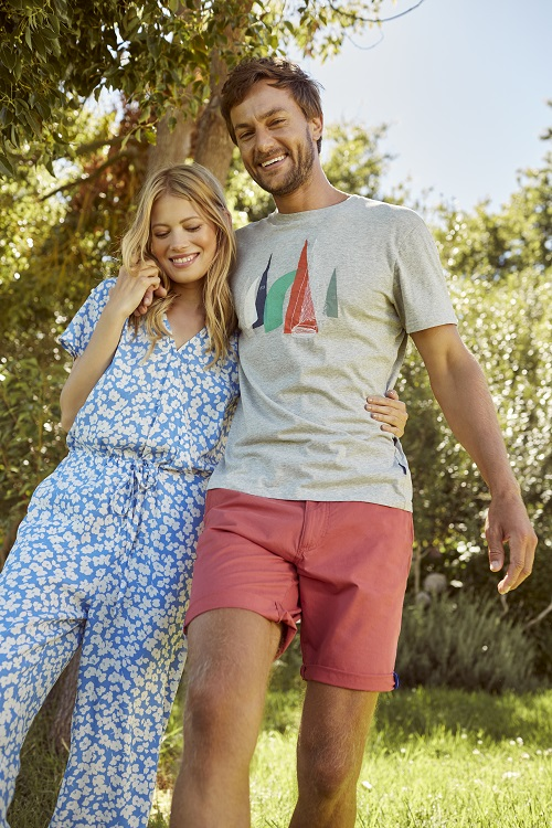 A man and a woman wearing spring clothing from Joules and walking with their arms around each other's shoulders.