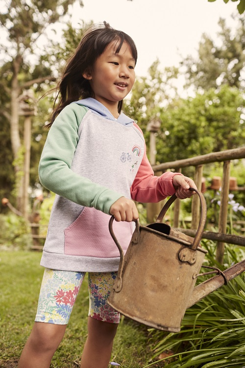 A young girl wearing a hoody and cycle shorts and holding a watering can.