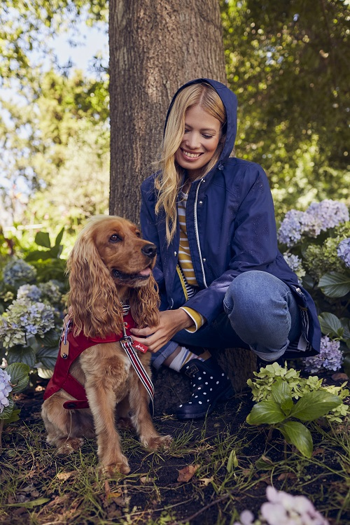 A woman wearing a blue hooded jacket and bending down to stroke a brown dog.