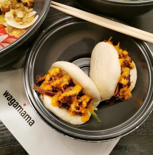 Steamed buns from wagamama in a take out box and chopsticks.