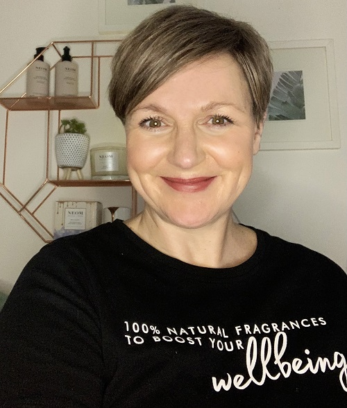 A smiling woman wearing a black top which says wellbeing.