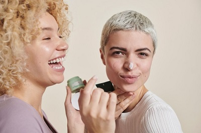 2 women using the Body Shop Aloe cream and laughing