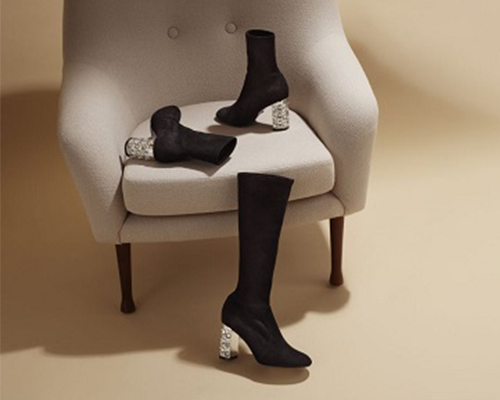 Black boots with silver heels on a chair.