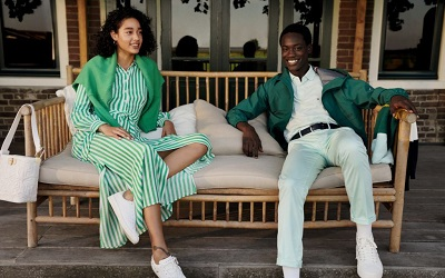 A woman and a man sat on a outside bench wearing green and white clothing.