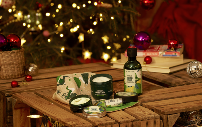 Some body shop products on a crate in front of a christmas tree.
