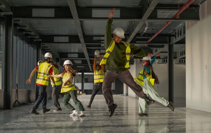 Six people are dancing in an empty building, they wear white hard hates and yellow high vis vests.