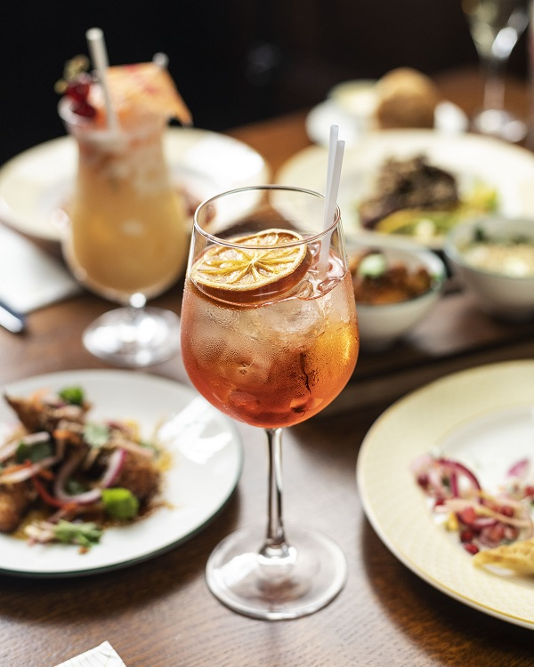 Aperol Spritz on table with dishes out of focus