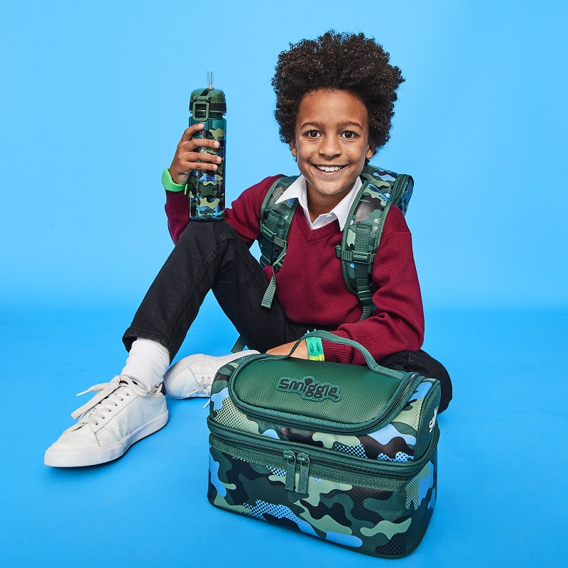A school boy wearing camo coloured back pack lunch bag and water bottle.