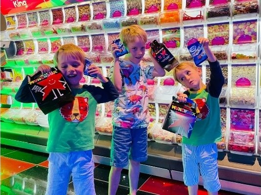 Three children holding snacks and sweets in front of a pic and mix stand.