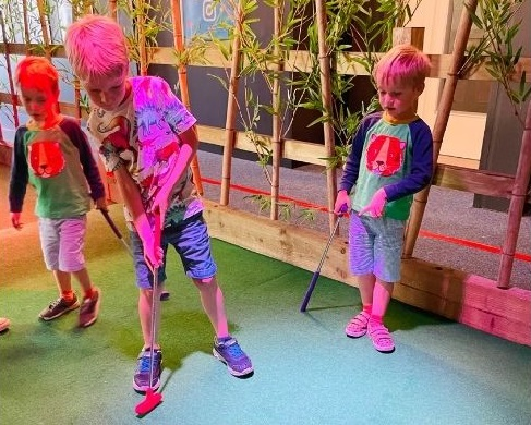 Three children playing mini golf at Paradise golf, Drake Circus.