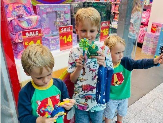 Three children hodling toys outside smiggle.