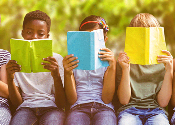 5 children sat with books in front of their faces.