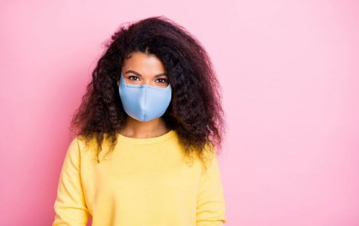 Young woman wearing a blue face mask standing in front of a pink background