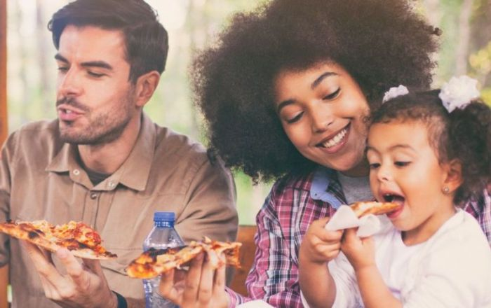 A family (mother, father, daughter) sitting eating pizza.