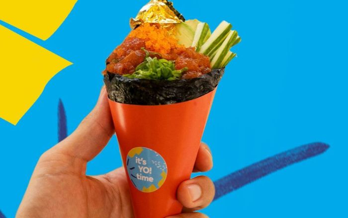 A cone shaped roll of sushi being held aloft.
