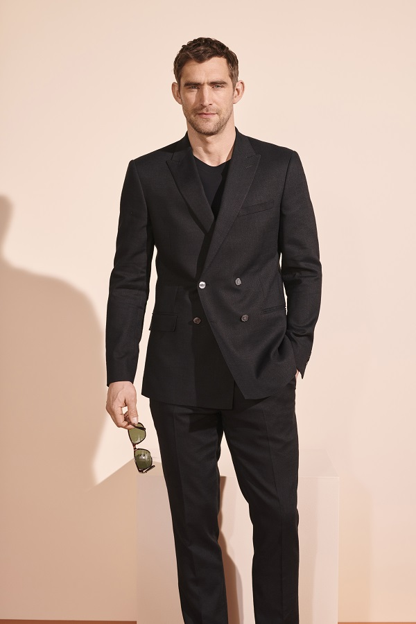 A man wearing a black suit from M&S.