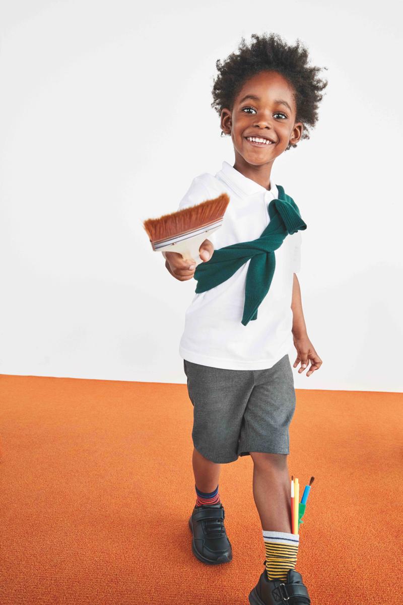 A school boy in uniform holding a paint brush.
