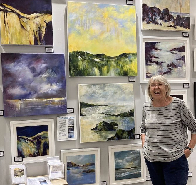 A woman standing in front of paintings on a wall.