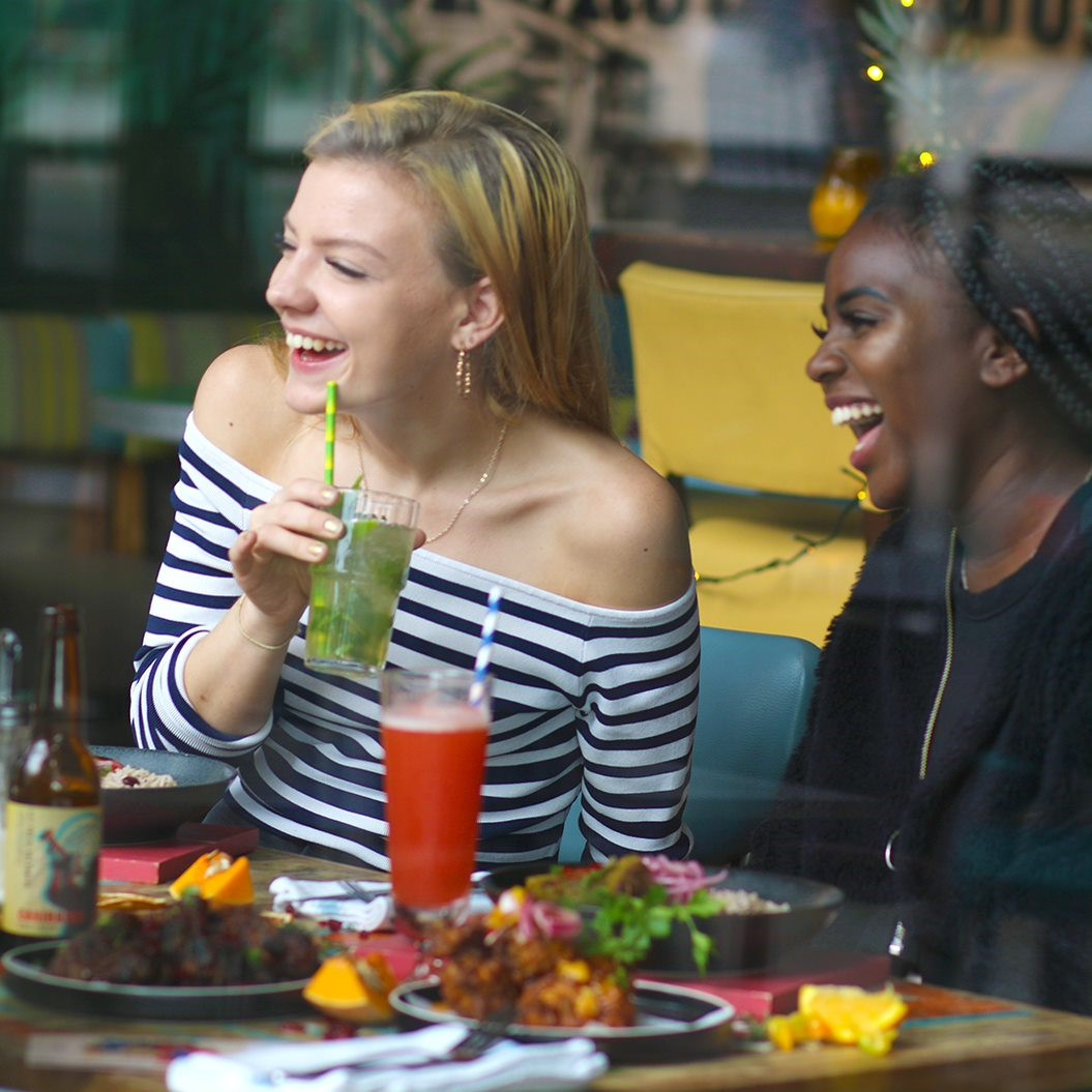 Two women eating Caribbean food and drinking cocktails at turtle bay