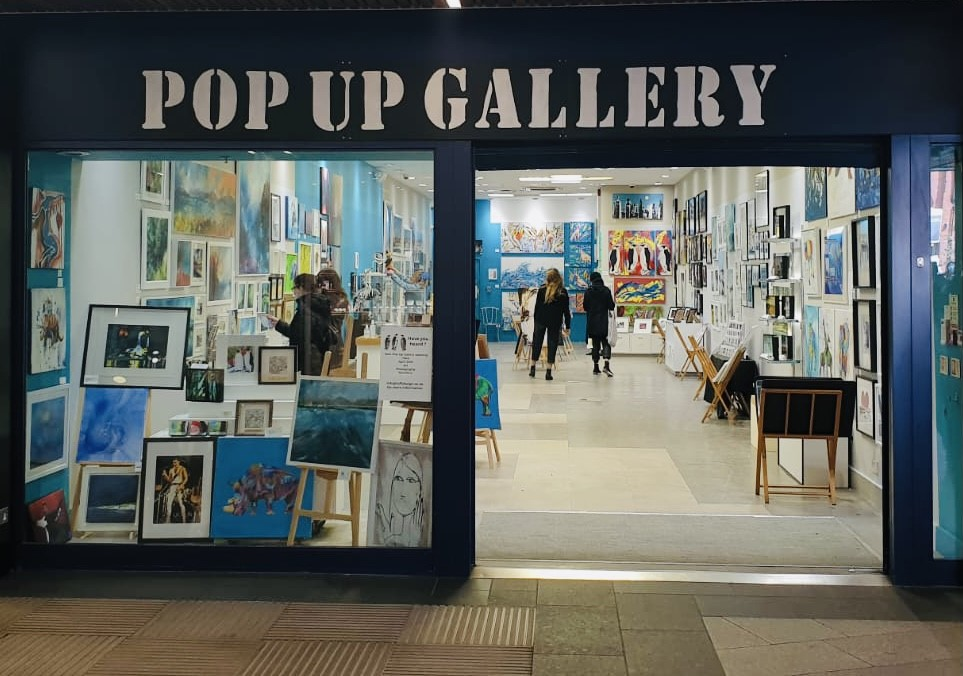 photo of front of art gallery with paintings in window and customers in store
