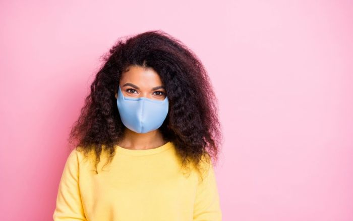 Young woman wearing a blue mask standing in front of a pink background