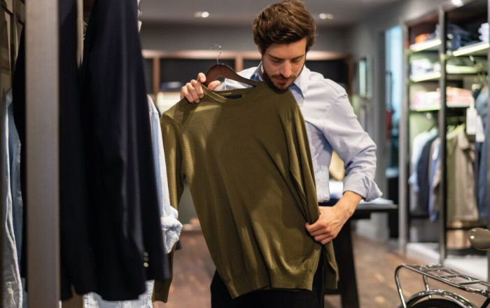 A man holding up a jumper in a shop