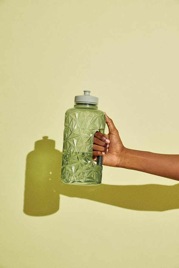 A hand holding a water bottle.