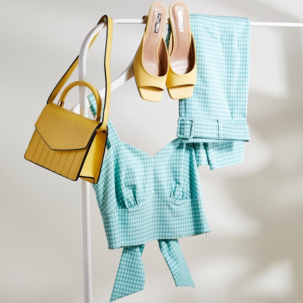 Turquoise top and trousers hanging from a rail with a yellow bag and shoes from Primark