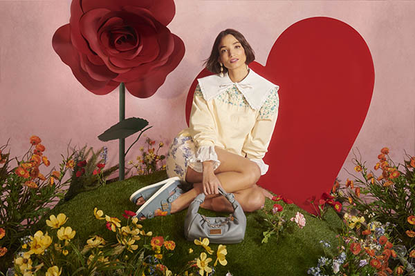 Woman sat on grass with flowers around her in front of a big red heart and rose background wearing clothes and accessories from River Island