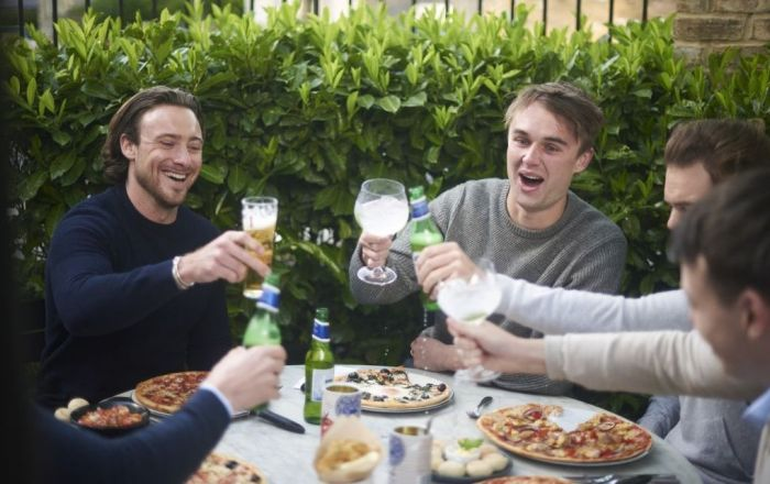 friends around a table eating pizza.