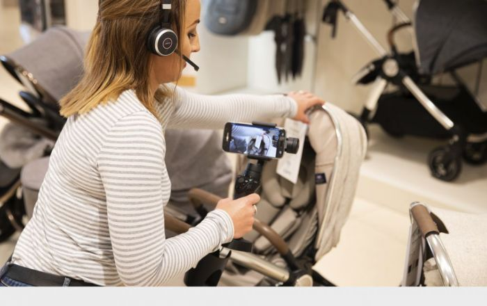 A woman wearing a headset and showing a pram via a mobile phone camera.