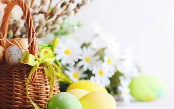 Wicker basket with eggs inside and green bow on the handle. Daisy flowers in the background and Easter decorated eggs next to the basket