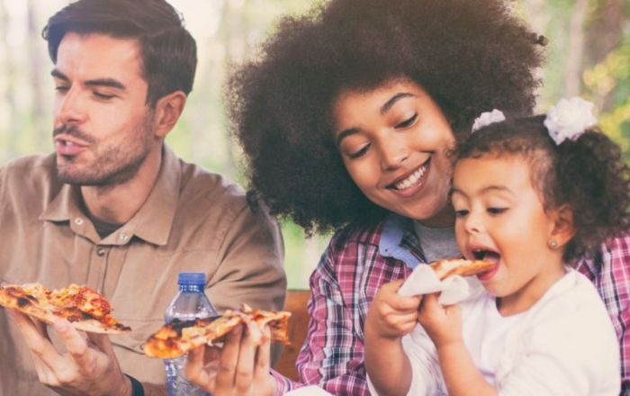 A couple eating pizza with their daughter outside