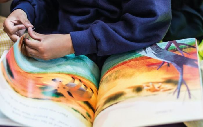A children's book open on a page with hands turning the page.