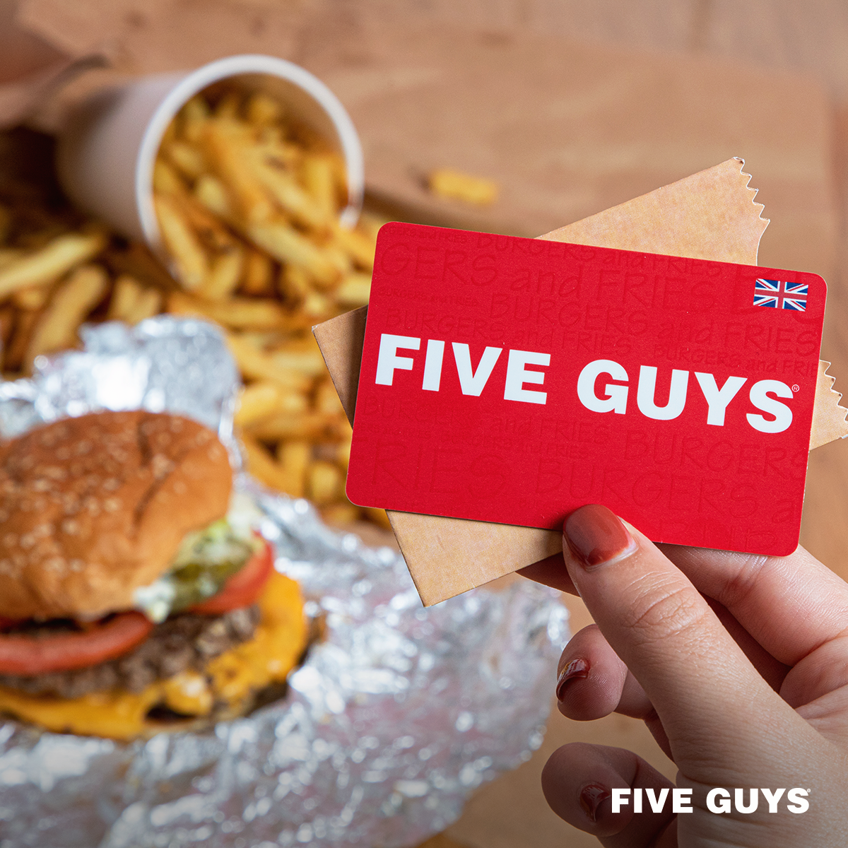 Five Guys burger and fries with a hand holding a card that says Five Guys in white text on a red background