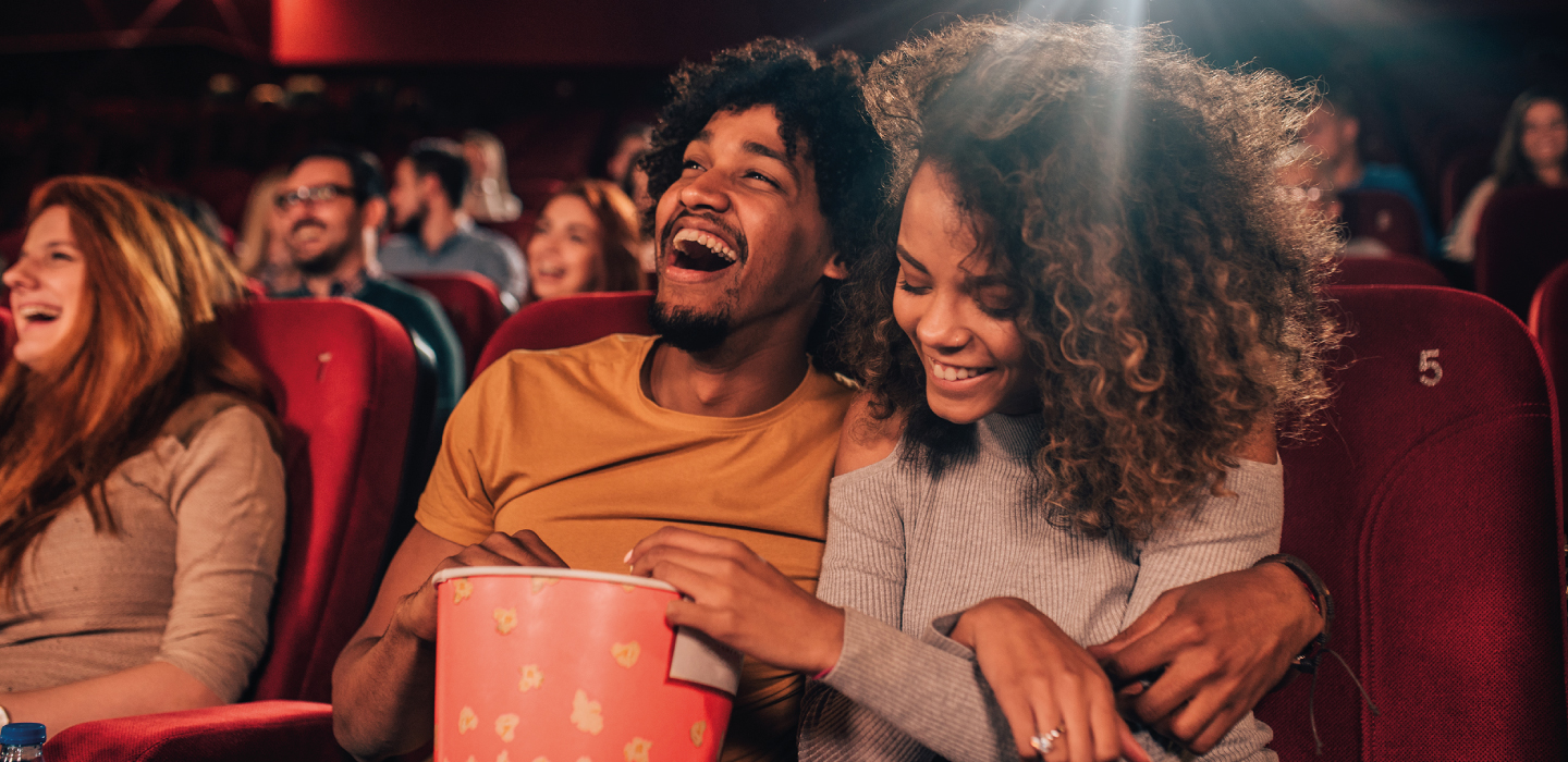 A couple laughing at the cinema in their seats with other people around them