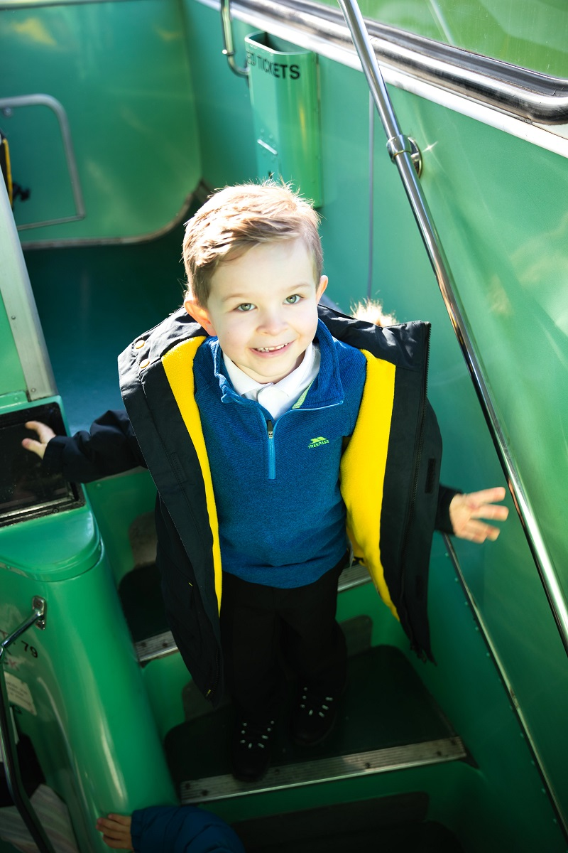 A boy on a schoolbus wearing a Trespass coat and jacket.