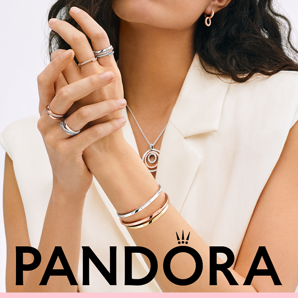 A woman wearing bracelets a necklace and rings from Pandora.