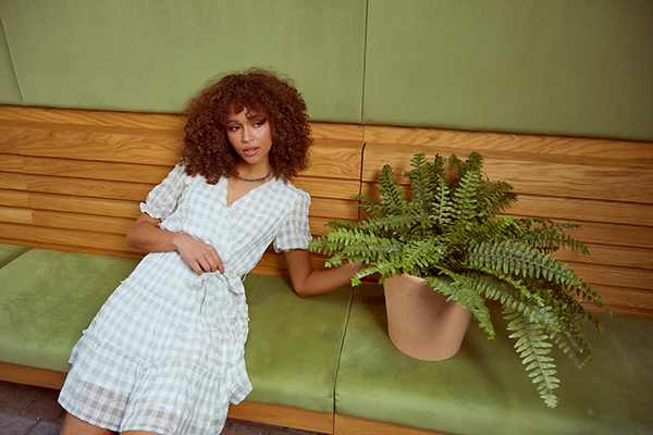Woman in Quiz dress sat on a bench next to a plant