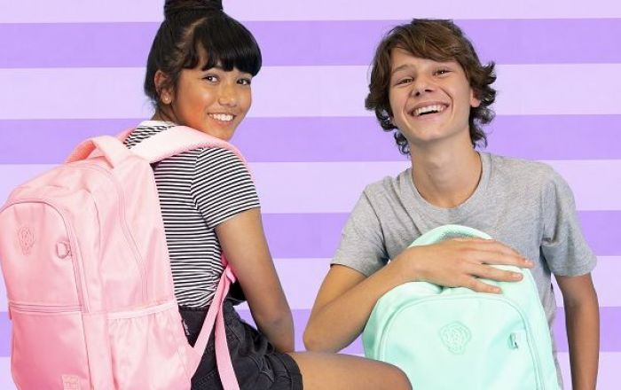 Two people wearing a pink and a mint green back pack.