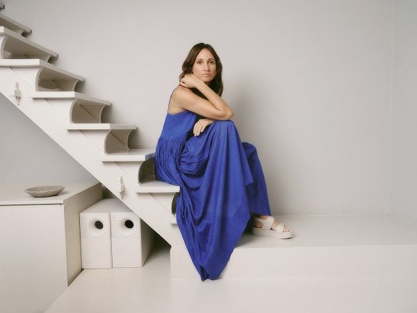 A woman sitting on a staircase and wearing a long blue dress and white sandals.