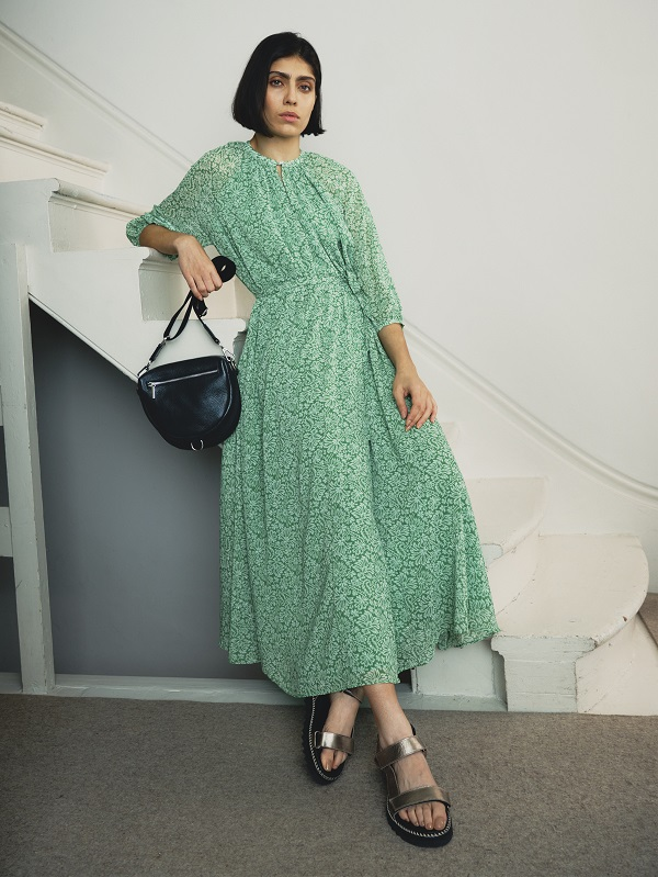 A woman wearing a long green floral dress and holding a black handbag.
