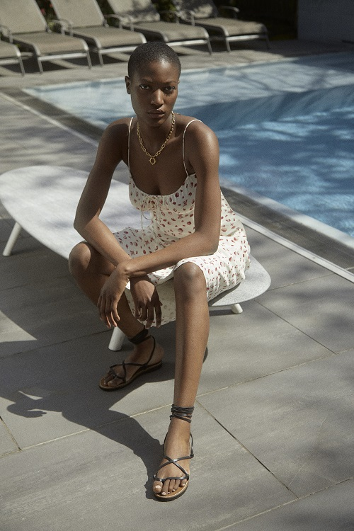 A woman wearing a white floral dress and black sandals.