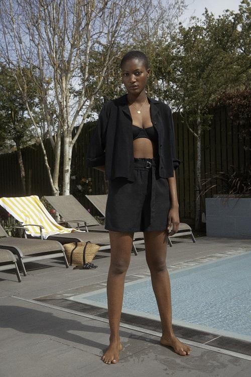 A woman wearing a black bikini top, shirt and skirt.