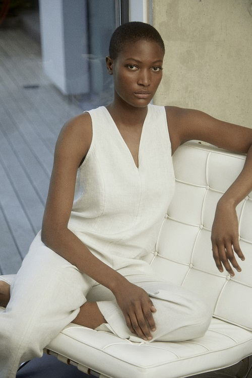A woman wearing a white jumpsuit