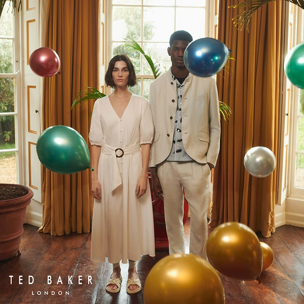 Two people wearing cream ted baker clothes standing in a room surrounded by colourful balloons.