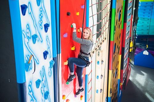 A woman climbing the wall at Rock Up.