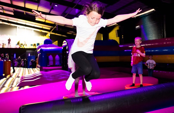A girl jumping on an inflatable at Air Haus.