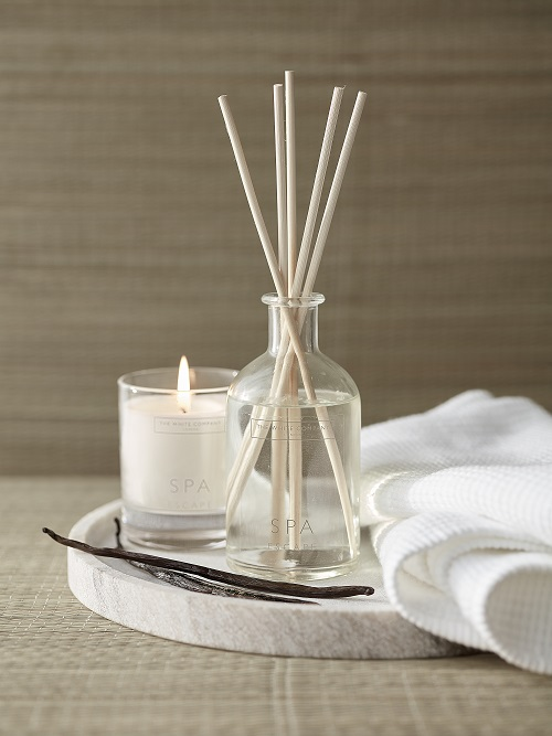 A white candle and a reed diffuser from The White Company